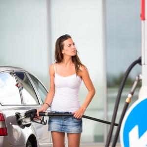 Woman refueling at pump.